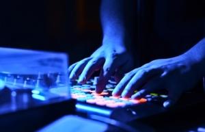 DJ's hand on audio mixer